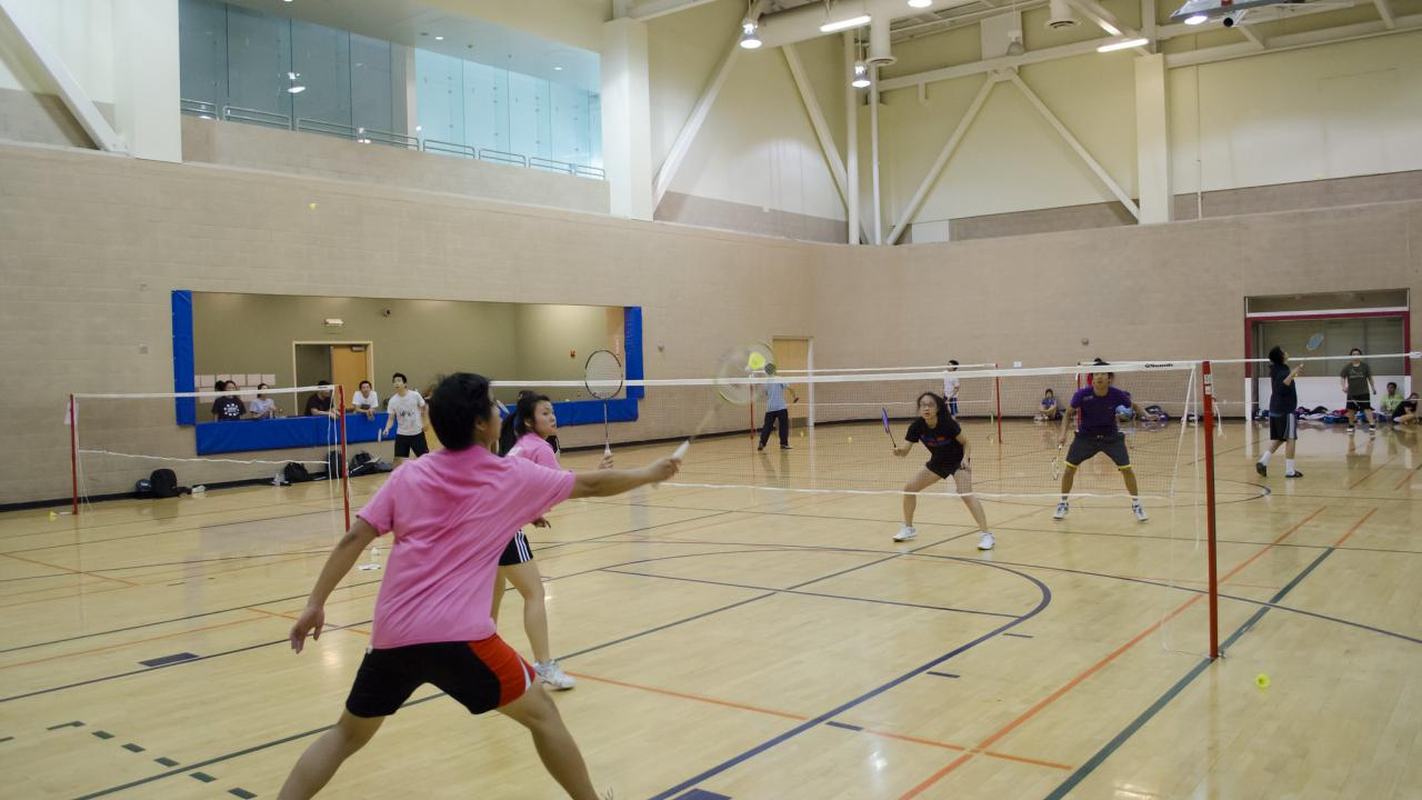 boy and girls playing badminton together in the gym