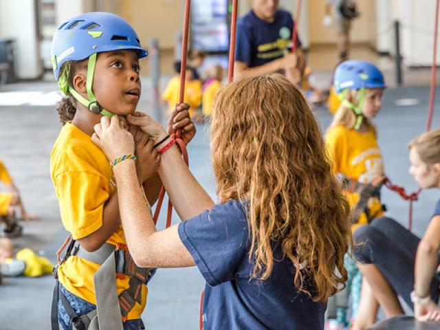 Woman helping child fasten helmet at climbing wall