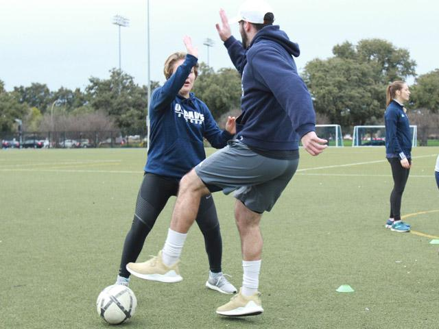 Young man and lady high fiving on soccer field