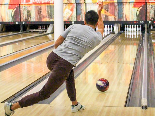 person bowling, ball partway down the alley.
