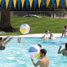 People swimming and throwing beach balls