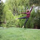 A dancer performing a leap in their backyard.