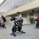 Masked students cycling outdoors in the ARC FitYard.