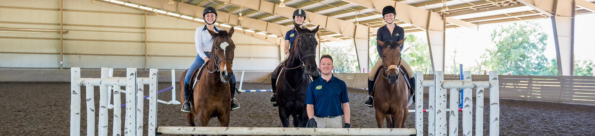 Equestrians posing in front of the camera alongside an instructor