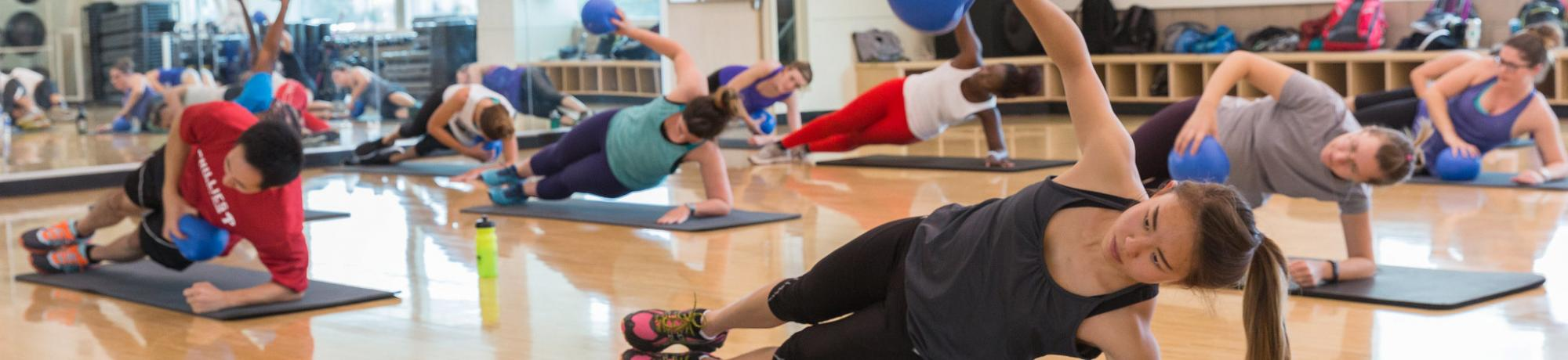 Students in exercise studio on yoga mats in side plank position holding small exercise balls